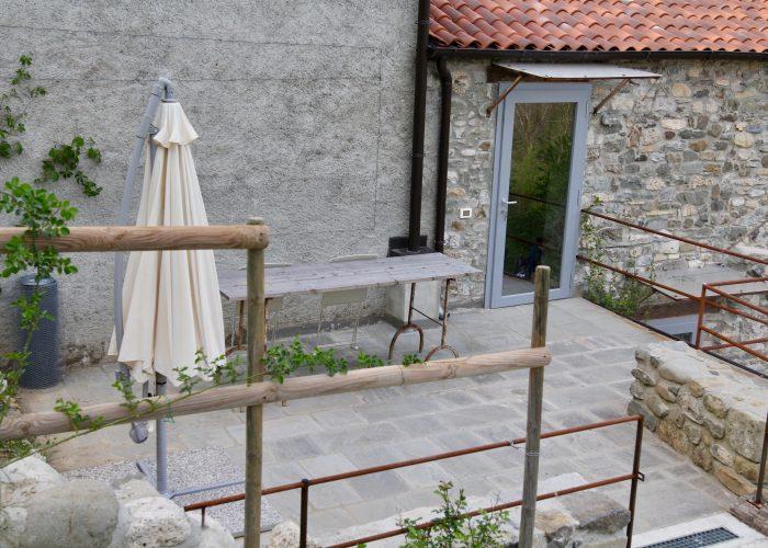 """Prima di entrare nella """"Casa di Sopra"""" abbiamo un angolo terrazza molto intimo con tavolo e ombrellone."""