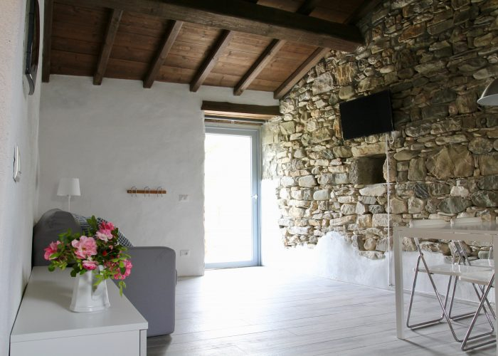 The living room/kitchen, entering from the main door, has a wide view on the Apuan Alps from one side and on the Borgo from the other side. The wall that separates from the Borgo church is made of exposed stones.